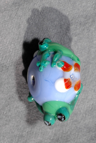 Two geckos on a bead with a flower